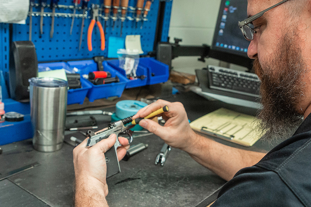 Gunsmith Sean Shipman making adjustments to a Walther PPK on his repair desk at Umarex/Walther in Fort Smith.
