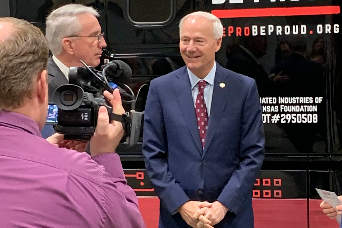 Gov. Asa Hutchinson answers a question as Arkansas State Chamber of Commerce President and CEO Randy Zook listens at the Be Pro Be Proud expo on Thursday.