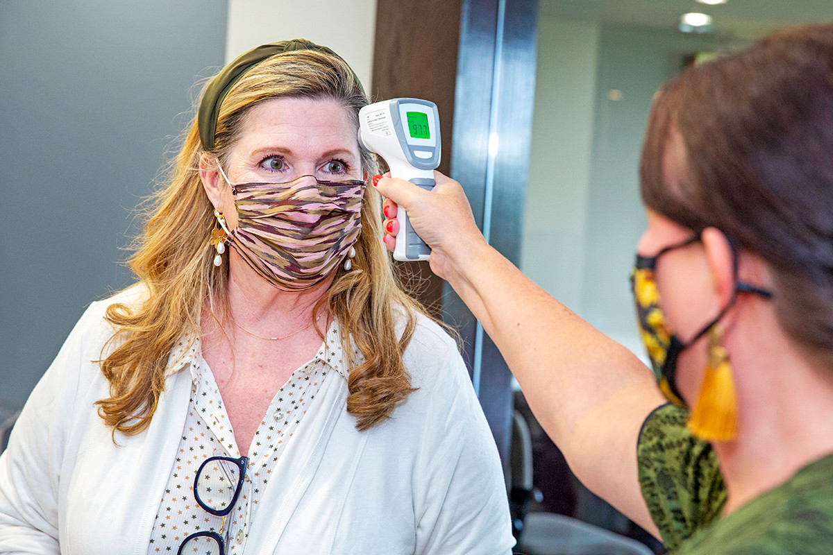 Office etiquette has expanded to embrace temperature checks as part of the COVID-modified reception routine. Kim Battle, director of property management at the Little Rock office of Colliers International, undergoes a Fahrenheit scan by Leslie Wilson, human resources director with Colliers.